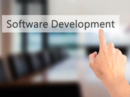 Software Development - Hand indrukken van een knop op onscherpe achtergrond concept. Business, technologie, internet concept. Stock foto Stockfoto