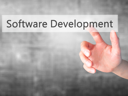 Software Development - Hand pressing a button on blurred background concept . Business, technology, internet concept. Stock Photo