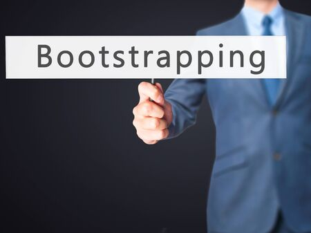 funded: Bootstrapping - Businessman hand holding sign. Business, technology, internet concept. Stock Photo
