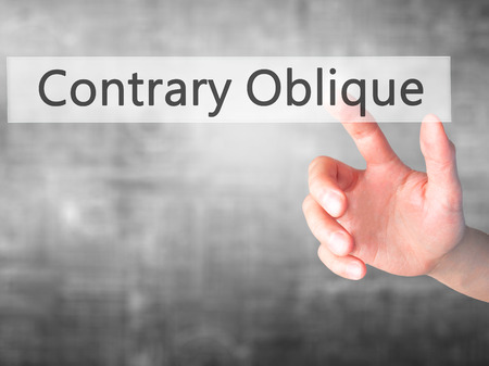opposites: Contrary - Oblique - Hand pressing a button on blurred background concept . Business, technology, internet concept. Stock Photo Stock Photo