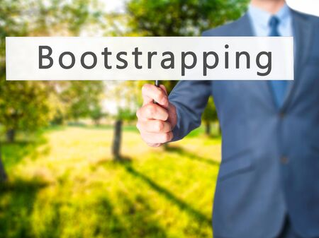 Bootstrapping - Businessman hand holding sign. Business, technology, internet concept. Stock Photo