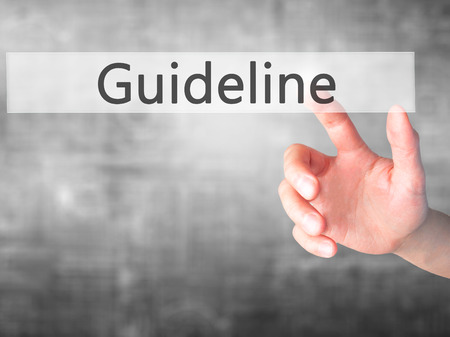 guideline: Guideline  - Hand pressing a button on blurred background concept . Business, technology, internet concept. Stock Photo Stock Photo