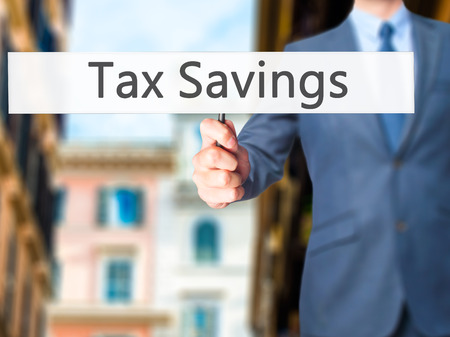 pay cuts: Tax Savings - Businessman hand holding sign. Business, technology, internet concept. Stock Photo