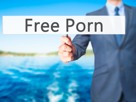 pornography: Free Porn - Businessman hand holding sign. Business, technology, internet concept. Stock Photo Stock Photo