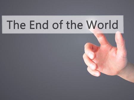 end of the world: The End of the World - Hand pressing a button on blurred background concept . Business, technology, internet concept. Stock Photo Stock Photo