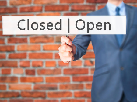 susceptible: Open Closed - Businessman hand holding sign. Business, technology, internet concept. Stock Photo