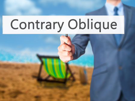contrary: Contrary - Oblique - Businessman hand holding sign. Business, technology, internet concept. Stock Photo