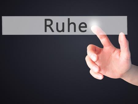 respectful: Ruhe (Quiet in German) - Hand pressing a button on blurred background concept . Business, technology, internet concept. Stock Photo