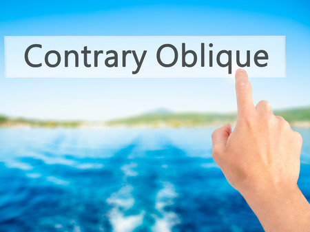 contrary: Contrary - Oblique - Hand pressing a button on blurred background concept . Business, technology, internet concept. Stock Photo Stock Photo