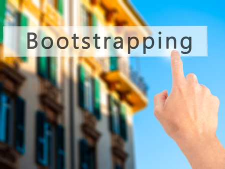 funded: Bootstrapping - Hand pressing a button on blurred background concept . Business, technology, internet concept. Stock Photo