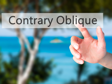 oblique: Contrary - Oblique - Hand pressing a button on blurred background concept . Business, technology, internet concept. Stock Photo Stock Photo