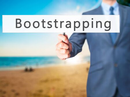 financed: Bootstrapping - Businessman hand holding sign. Business, technology, internet concept. Stock Photo