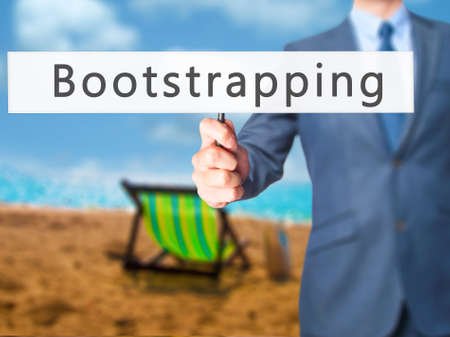 bootstrap: Bootstrapping - Businessman hand holding sign. Business, technology, internet concept. Stock Photo