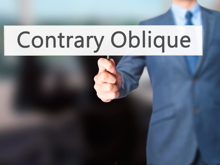 opposites: Contrary - Oblique - Businessman hand holding sign. Business, technology, internet concept. Stock Photo