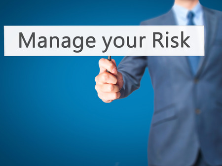 comply: Manage your Risk - Businessman hand holding sign. Business, technology, internet concept. Stock Photo