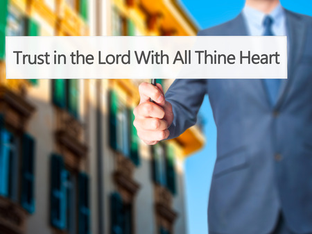 credence: Trust in the Lord With All Thine Heart - Businessman hand holding sign. Business, technology, internet concept. Stock Photo