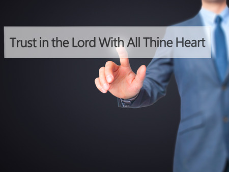 credence: Trust in the Lord With All Thine Heart - Businessman hand pressing button on touch screen interface. Business, technology, internet concept. Stock Photo