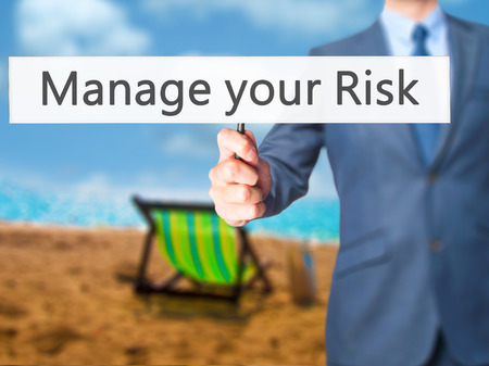 losing control: Manage your Risk - Businessman hand holding sign. Business, technology, internet concept. Stock Photo