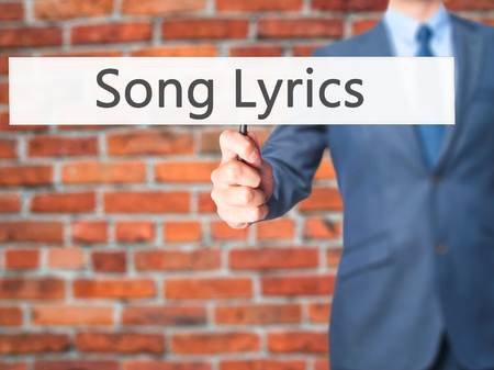 lyrics: Song Lyrics - Businessman hand holding sign. Business, technology, internet concept. Stock Photo Stock Photo