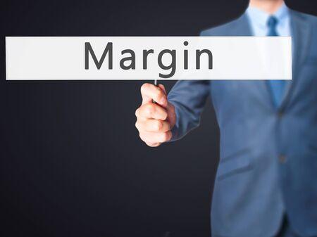 margin: Margin - Businessman hand holding sign. Business, technology, internet concept. Stock Photo