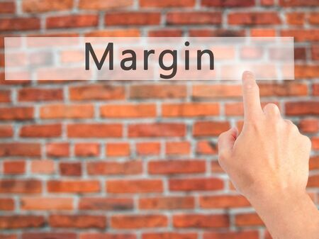margen: Margin - Hand pressing a button on blurred background concept . Business, technology, internet concept. Stock Photo