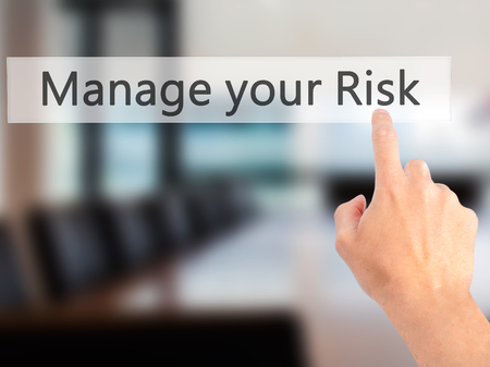 losing control: Manage your Risk - Hand pressing a button on blurred background concept . Business, technology, internet concept. Stock Photo
