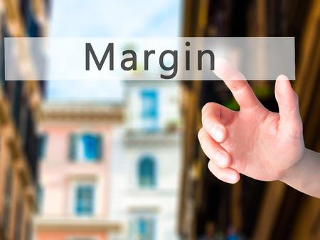 margen: Margin - Hand pressing a button on blurred background concept