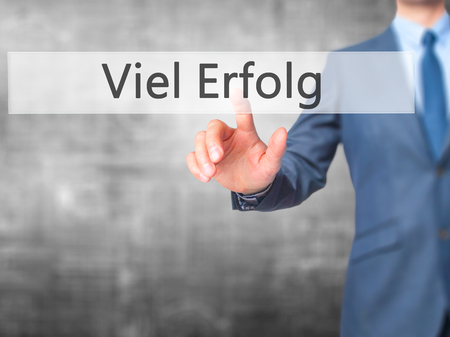 Viel Erfolg (Much Success In German) - Businessman hand pressing button on touch screen interface. Stock Photo