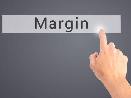 margen: Margen - Mano presionando un botón en concepto de fondo borroso Foto de archivo