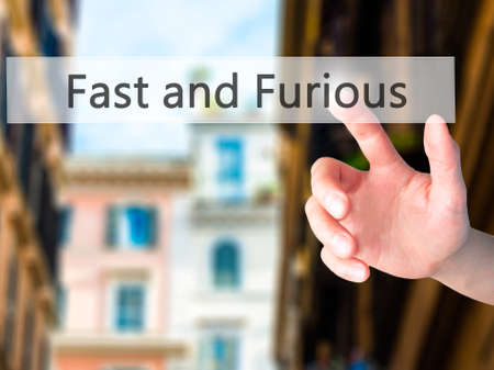 fastness: Fast and Furious - Hand pressing a button on blurred background concept . Business, technology, internet concept. Stock Photo
