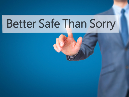 better safe than sorry: Better Safe Than Sorry - Businessman hand pressing button on touch screen interface. Business, technology, internet concept. Stock Photo Stock Photo