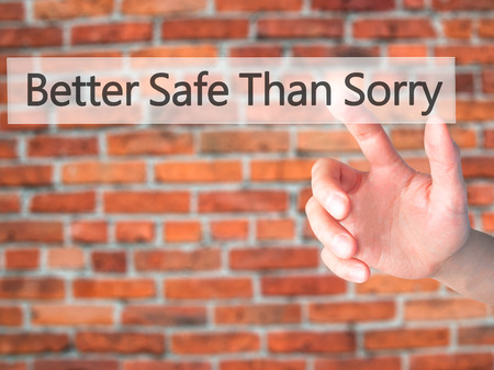 than: Better Safe Than Sorry - Hand pressing a button on blurred background concept . Business, technology, internet concept. Stock Photo