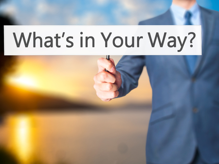 persevere: Whats in Your Way - Businessman hand holding sign.