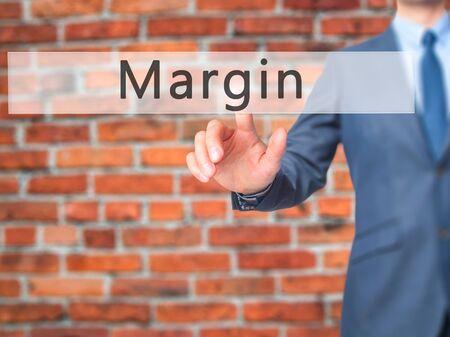 margen: Margin - Businessman hand pressing button on touch screen interface. Foto de archivo