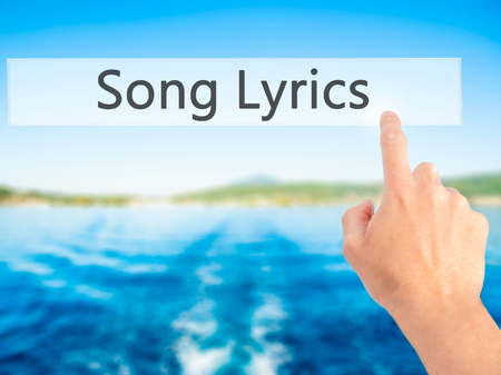 lyrics: Song Lyrics - Hand pressing a button on blurred background concept