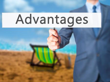 advantages: Advantages - Businessman hand holding sign. Business, technology, internet concept. Stock Photo