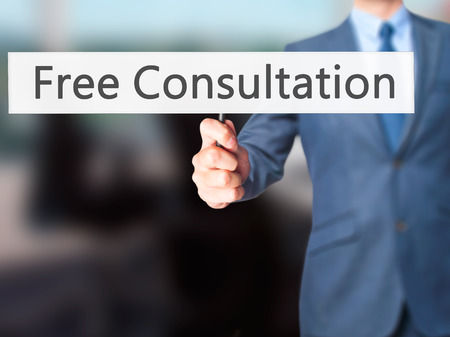 health answers: Free Consultation - Businessman hand holding sign. Business, technology, internet concept. Stock Photo