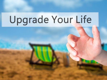 life extension: Upgrade Your Life - Hand pressing a button on blurred background concept . Business, technology, internet concept. Stock Photo