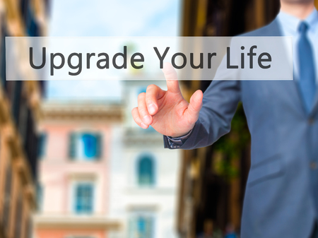 life extension: Upgrade Your Life - Businessman hand pressing button on touch screen interface. Business, technology, internet concept. Stock Photo