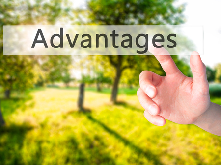 advantages: Advantages - Hand pressing a button on blurred background concept . Business, technology, internet concept. Stock Photo