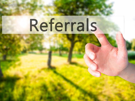 referrals: Referrals - Hand pressing a button on blurred background concept . Business, technology, internet concept. Stock Photo