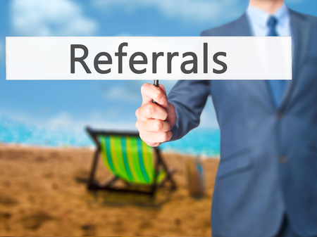 referidos: Referrals - Businessman hand holding sign. Business, technology, internet concept. Stock Photo