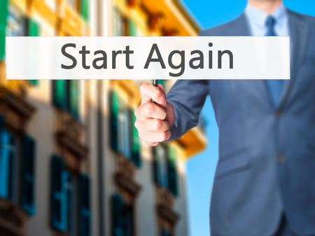 commence: Start Again - Businessman hand holding sign. Business, technology, internet concept. Stock Photo