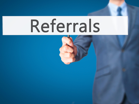 referrals: Referrals - Businessman hand holding sign. Business, technology, internet concept. Stock Photo