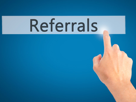 referidos: Referrals - Hand pressing a button on blurred background concept . Business, technology, internet concept. Stock Photo