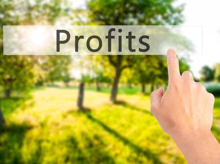 businessplan: Profits - Hand pressing a button on blurred background concept . Business, technology, internet concept. Stock Photo