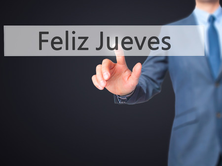 the thursday: Feliz Jueves (Happy Thursday In Spanish)  - Businessman hand pressing button on touch screen interface. Business, technology, internet concept. Stock Photo Stock Photo