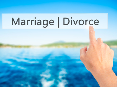 severance: Marriage  Divorce - Hand pressing a button on blurred background concept . Business, technology, internet concept. Stock Photo