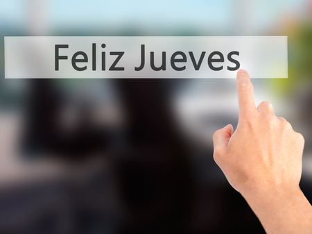 the thursday: Feliz Jueves (Happy Thursday In Spanish)  - Hand pressing a button on blurred background concept . Business, technology, internet concept. Stock Photo