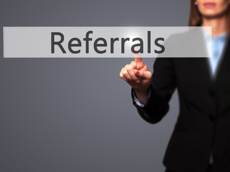 referrals: Referrals - Businesswoman hand pressing button on touch screen interface. Business, technology, internet concept. Stock Photo